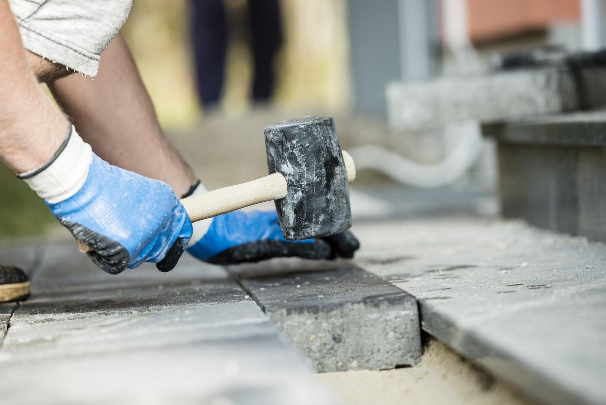Workman laying a paving stone or brick